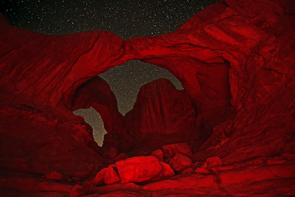 """SEEING MORE RED AT ARCHES NP - 23 January 2015<br /> <br /> Double Arch in Red Light - Arches National Park, File# 1515290<br /> <br /> Link to Full Sized Image:  <a href=""""http://www.tom-hill.biz/Galleries/Scenics/Utah/i-XJS8DNC/A"""">http://www.tom-hill.biz/Galleries/Scenics/Utah/i-XJS8DNC/A</a><br /> __________<br /> <br /> (Editor:  Updated with some typo fixes - 23 Jan 15)<br /> <br /> This red light thing where I bath the subject with a red light from a handheld flashlight is a new thing.  I think it looks cool though like any fad, it might be a flash in the pan.  After doing it a few times like eating a bowl of CoCo Puffs, it might feel great at the time but after reflection you might not be so proud of it.<br /> <br /> I am not there, yet, with using a red light to modify the light in such a dramatic way.  I'm not at the """"not so proud"""" stage, yet.  I still think it's cool to be able to capture a subject like the Double Arch that otherwise would be a black blob... nothing in the dark.  At least using this technique makes the subject interesting and it's something.<br /> <br /> So it goes with the creative process.  Photography is no different from any other form of creativity.  Some people think that photography is all about capturing reality.  While you can very closely document instants in a flow of life, it's not precisely reality.  It's just a photo.  I believe the medium allows for creativity.  In fact, to be relevant experimentation is required or the art form becomes stale.<br /> <br /> If you look at what I like to shoot, nature images, you'll find most nature photos pretty similar across the board.  It's hard to make unique and impactful art when your subject is so obviously real.  To overcome that, there are those that try to turn up the saturation in post processing to made the colors more vibrant and bold in the final image.  Super bright highly saturated colors can be quite attractive, in a """"I can't turn my eyes away"""" kind of way.  Unfortunately, the"""
