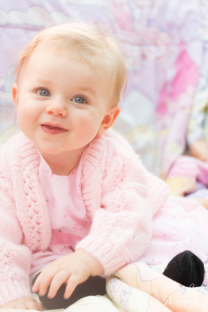 Baby girl dressed in pink, sitting up infront of pastel background