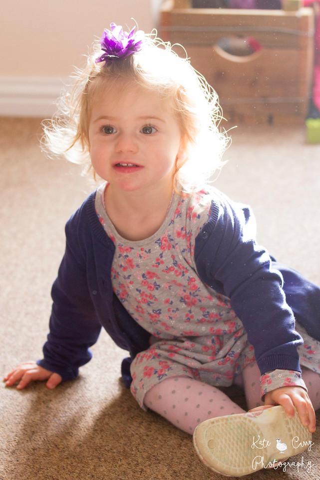 Toddler in purple, sitting in sunshine