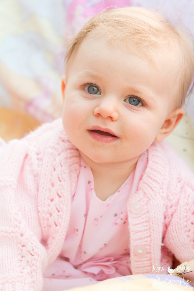 Baby girl dressed in pink, infront of pastel background