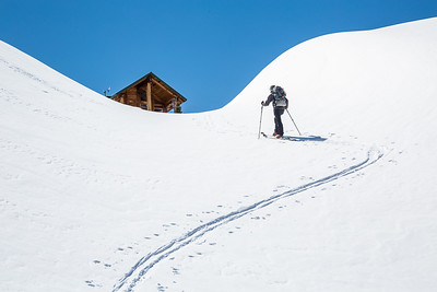 Skier skinning uphill, hiking toward a backcountry ski hut in the Rocky Mountains of British Columbia, Canada.