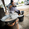 a local Thai woman enjoying her lunch as she renders down coconut sugar