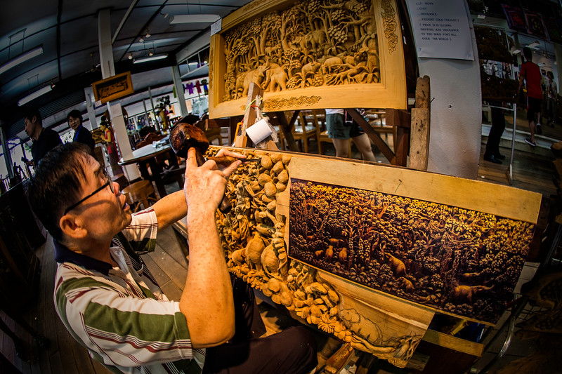 an artist at The Floating Market, creating a stunning wood carving