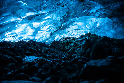 Ice cave under glacier, glowing blue from sunlight above