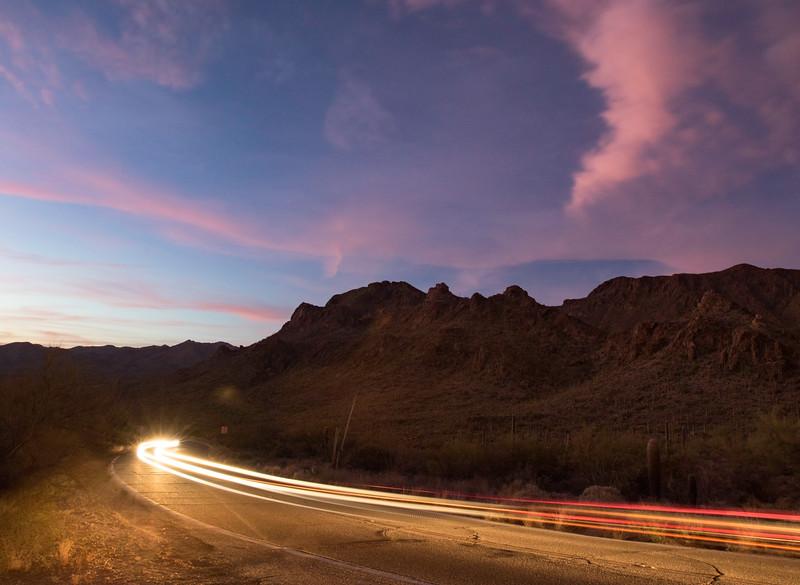 Cars going through Gates Pass outside of Tucson, AZ at sunset. 2 photo panorama