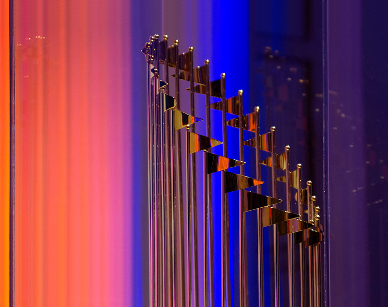 The gold of the Houston Astros 2017 World Series Champion trophy reflecting the surrounding orange and blue lights at the Houston Museum of Natural Science
