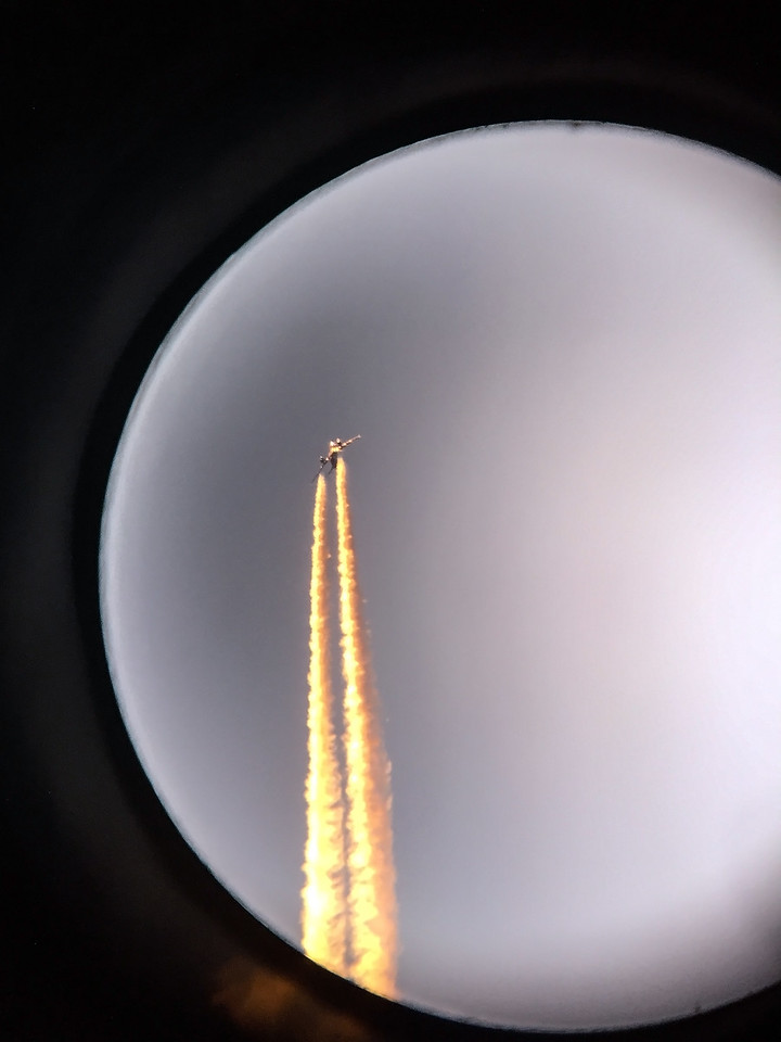 """The contrails from a plane lit up at sunset make it look like a rocket. Taken through a 10"""" telescope at San Jacinto College South."""