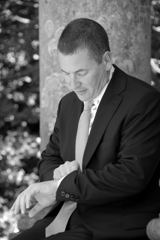 Time check! We all know brides like to keep grooms waiting. But it can be a cruel wait. Ushers are there to lghten the mood. Lloyd Boyd waiting for Katherine at The National Trust's Temple of Apollo, Stourhead.