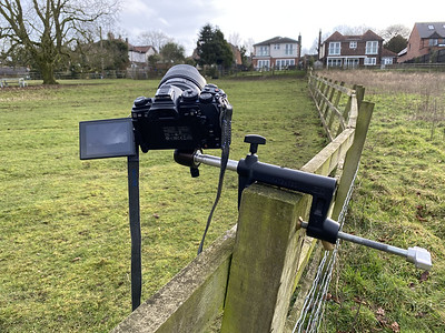 Olympus camera/lens mounted on clamp on fence.
