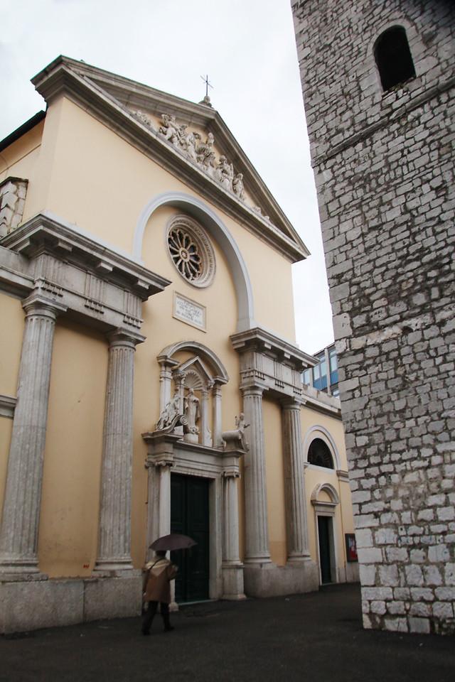 A passerby walks past a church in Rijeka, Croatia.