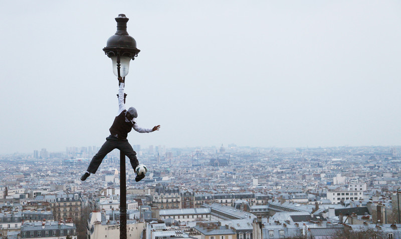 A street performer hangs from a lamp post while balancing a soccer ball and smoking a cigarette in Paris, France.