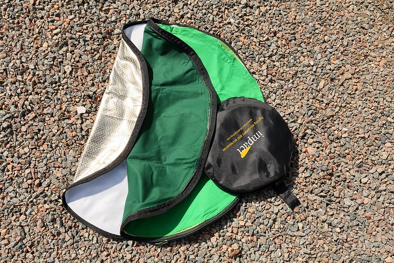 "Custom Impact 5-1 32"" photo disc covering showing the original gold-and-silver side, original reflective white side, my custom dark green fabric side, and my custom light green fabric side, with storage bag on top."