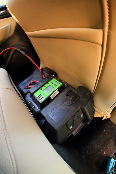 The 50 Amp-Hour battery housed in a marine battery box with the charge controller fastened to the top and connected to the solar panel on the roof. The outlet I installed in the box to power the cooler is visible at the near end.