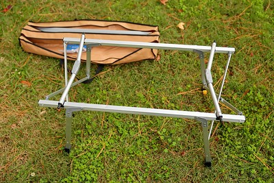 Folding aluminum table base set up with top still folded in bag.