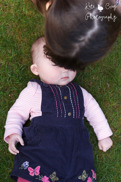 Photo of baby girl on lawn, Musselburgh, being interrupted by big sister.
