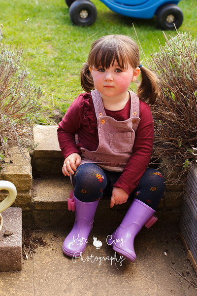 Preschool girl in pigtails, sitting on steps outside, Musselburgh.