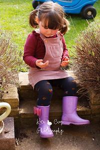 Preschool girl in pigtails, sitting on steps outside, Musselburgh,