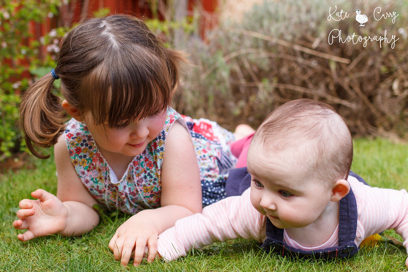 Preschool girl in pigtails holding hands with her baby sister outside, Musselburgh.