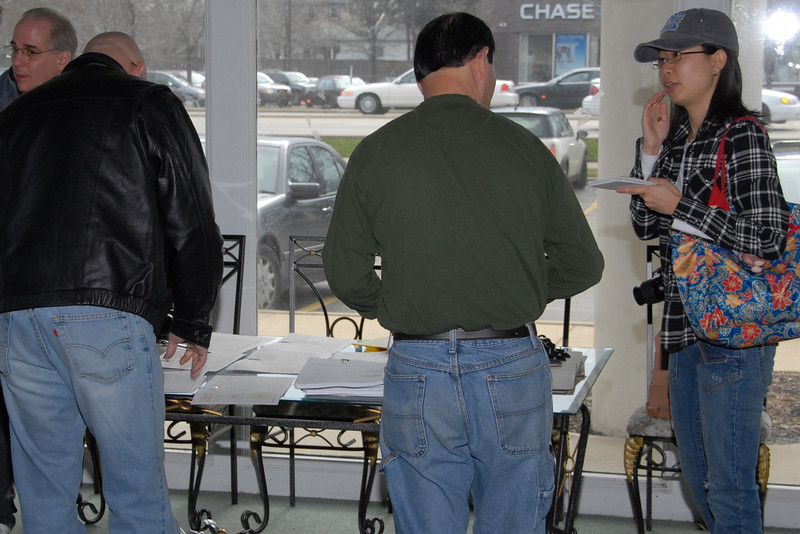 People pick up survey and flier packets before walking the neighborhood in Arlington Heights as part of the effort to save International Plaza from eminent domain abuse.  The young lady at right is a reporter who showed up to cover the effort.  (1/6/2007)
