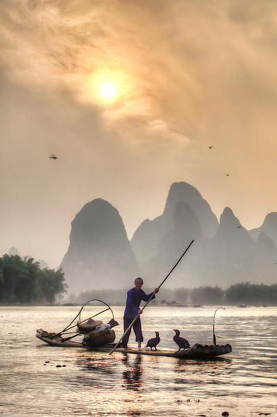 Surreal Guilin  I was hanging out on a sandbar in the middle of the Li River, waiting for sunset when this fisherman happened to pass by. The sky was a crazy shade of yellow and the clouds surrounding the sun made it seem like some sort of solar explosion. Neither the fireflies, nor the fisherman and his two trusty cormorants seemed concerned that the sky was on fire. It was such a surreal landscape with the huge Guilin mountains in the background that I felt some sort of displacement of consciousness. Experiences such as these are a constant reminder to me that traveling is always worth all the minor inconveniences.