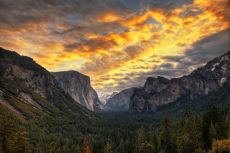 Fire Over Yosemite Valley  I recently posted a similar portrait of Yosemite Valley, so I thought I would also post the landscape shot.  This was taken as the sun was rising and the sky began to light up with warm colors.  I am still in awe of this incredible national park.  I wish I could move my family into a little log cabin and spend the year fishing, taking pictures and enjoying the scenery, but I think my wife and daughter would not appreciate that very much.