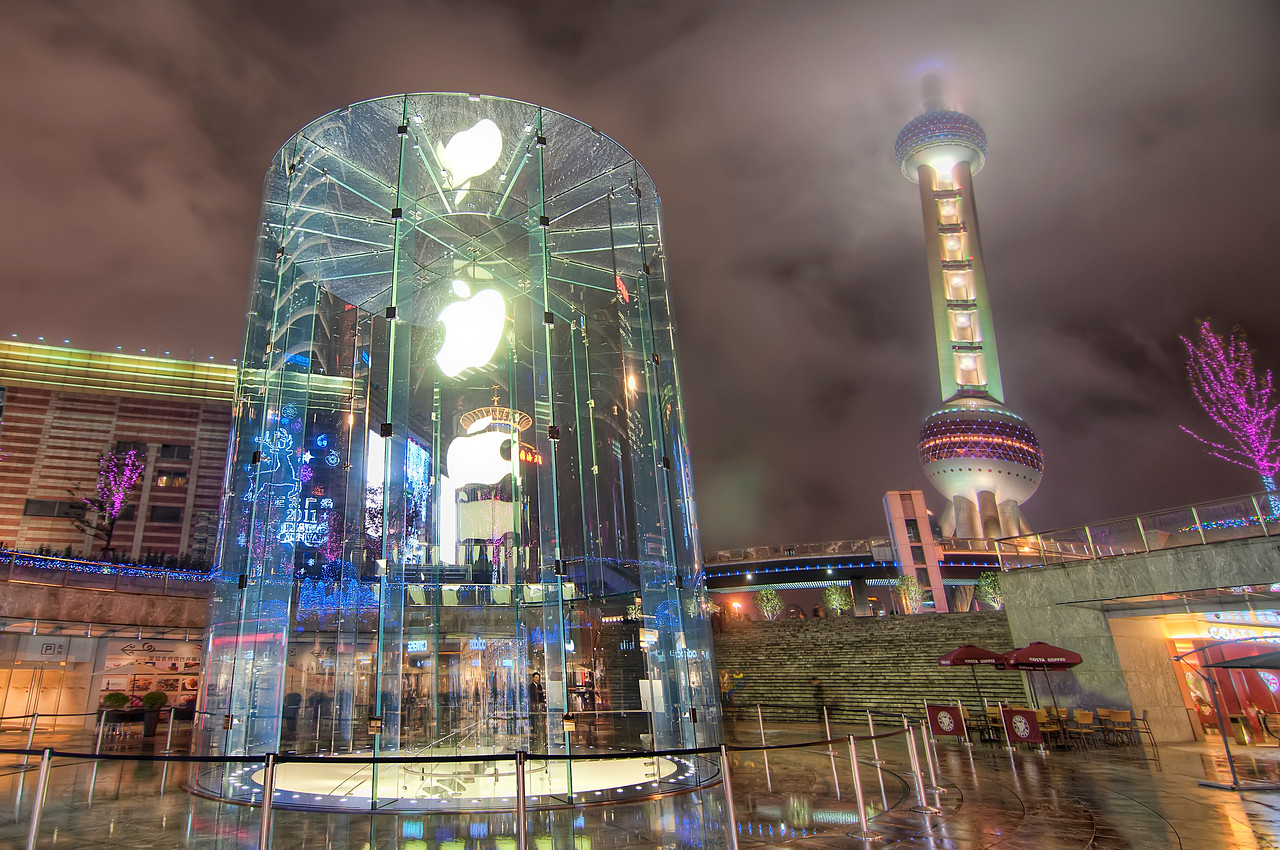 The Apple in the Crystal Jar  I was in Shanghai this past December and I tried to get out every evening to see if I could find some cool places to photograph.  It was mostly a bust though. One day I took a taxi to the abandoned apocalyptic mess that was once the World Expo and I ended up walking for a couple of hours in the cold, dark and rainy streets before I called it a day and went back to my hotel to lick my wounds.  On my last night in Shanghai, I went back to the popular side of town where all the super trendy people go shopping and I saw this Apple store.   As I was looking for a good angle I noticed the security guy at the entrance to the store mad dogging me.  I gave him a goofy wave and smile and just kept taking pictures until he started to come over.  I waited until he was half way between me and the entrance to his lair before I picked up my tripod and pretend to walk away.  As soon as he tuned back, I set my tripod back down and waited for him to realized he had been bamboozled.  He made it all the way back to his post before he noticed me!  He had a look of shock as he saw me wave at him in naked defiance.  I leisurely finished taking my pictures and then walked into the same store he was guarding.  Hehe.