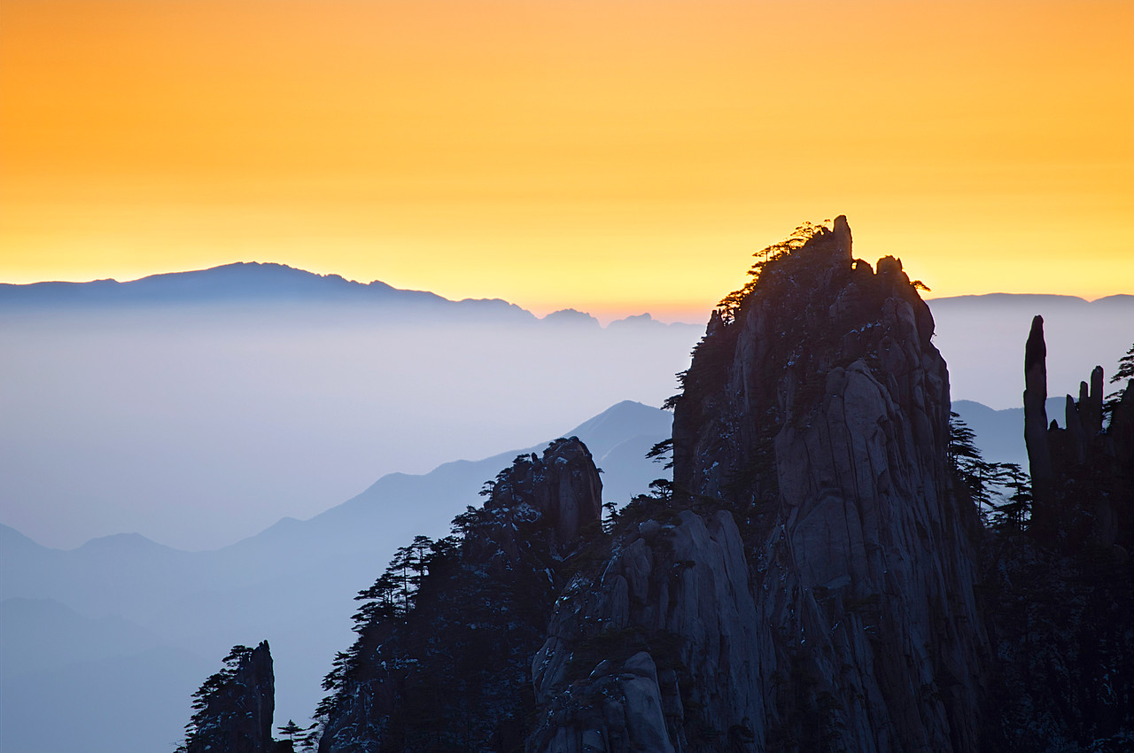 Gentle Rise  This was a peaceful sunrise at the amazing Yellow Mountains in China.  I had gotten there the night before and scoped out the area for the best places to catch the sun rising.  I woke up at an unholy hour to get here before the billions of tourists changed out of their jammies and clogged up all the vantage points.  It was a very short trip but well worth it.