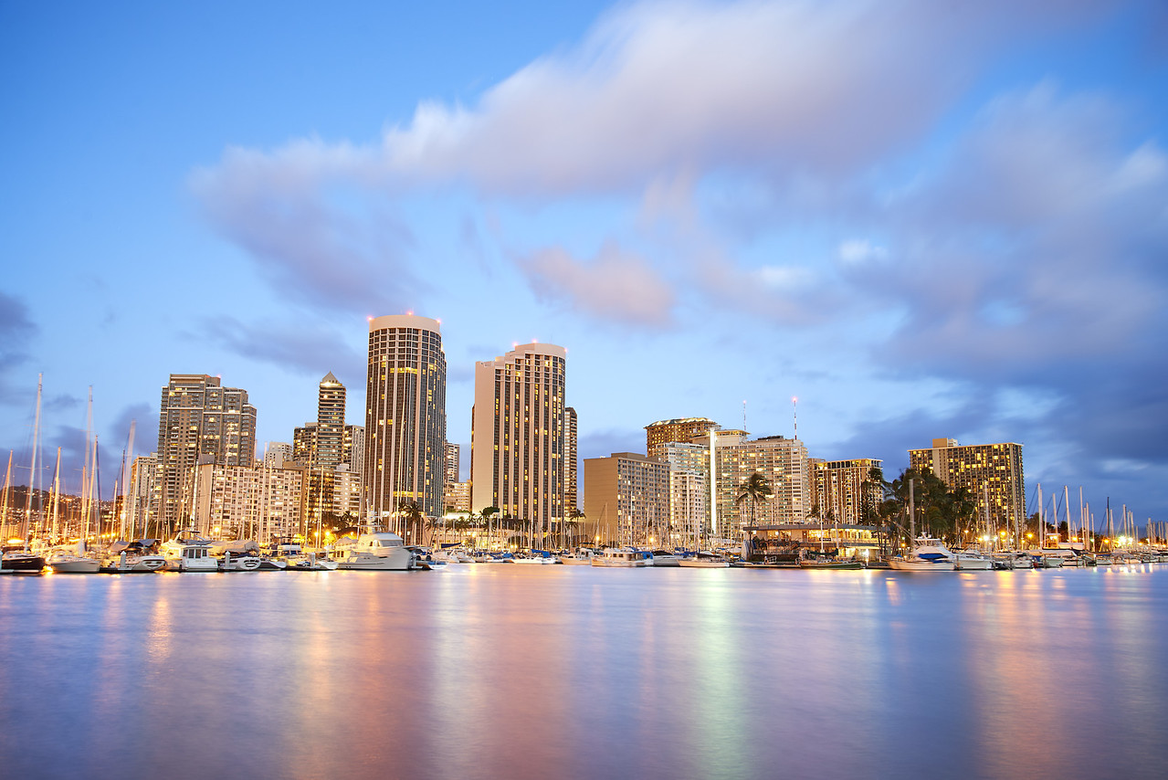 Oahu Skyline  I was watching the day come to a rest on the edge of Magic Island on Oahu as the lights inside the buildings were coming on and the sky was turning a nice deep blue color.  I had originally wanted to get take this photo of the Oahu Skyline during the blue hour but I noticed that the sky still had a nice hint of pastel colors.   I thought it would be cool to accentuate the pastel colors while the city lights were turned on so I over-exposed the shot and left the shutter open for a few seconds.  That gave this picture a surreal feel as the city lights at dusk clash with the bright sky.  I am not sure if it works or not, but it plays a trick on the visual mind for long enough to make it interesting.  What do you think?