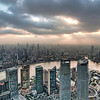 "The Megalopolis<br /> <br /> My previous attempt to make it up to Jin Mao Tower by sunset was foiled when our driver took a wrong turn and deposited us into the 9th circle of Shanghai-traffic hell. We were nearing the end of our stay in China and I still had not gotten any ""I am looking down on you mere mortals"", shots so I was extra determined to get here. On this day, I had already dragged my family to Suzhou and back and we were dangerously low on fun-happy-sparkles-energy because our last meal had been over fourteen hours ago (except for the baby, she eats a man-sized meal every two hours).  The baby gave me an annoyed look as I used her as an excuse to bypass the huge line to the elevator that took us to the observation deck. A quick ride up to the top and the doors opened up to reveal pandemonium.<br /> <br /> There were droves of Chinese tour groups, school kids and guides with megaphones waving those silly flags around. It was a photographer's nightmare. I found a place for my family to sit down while I squeezed through hot, sweaty masses of people to finally find this spot. I waited for the light to be just right, fired off a few shots and got the heck out of there. Even as we were in the elevator just about to escape the craziness, an old man decided to jump out as the doors were closing. Oh man …<br /> <br /> I wish I could say the rest of the evening went any better, but we ended up spending over $100 dollars on crappy food at a fancy restaurant and having to make a quick exit as the baby's good will finally ran out and she let us have it. My poor family endured a lot to get this shot, but now that a few weeks have gone by and emotions are no longer raw, they saw the final product and begrudgingly decided it was worth it. Thanks for your patience ladies. Enjoy the view of Shanghai's sprawling megalopolis at your leisure. =P<br /> <br /> … this photo looks awesome on a big screen … you can almost see the big boss through the window, yelling at his employees in the building 30 miles away."