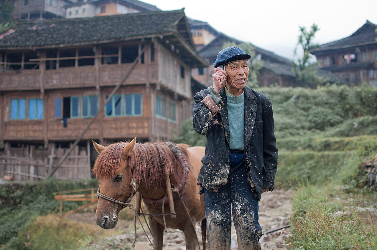 Farmer Ruins My World View (Longsheng Rice Terraces) I came across many rural farmers while traveling through the Longsheng (Dazhai ) rice terraces in China who have been working the land and eking out a living like countless generations before them had.  I remember that I had woken up stupid early to squeeze in as much photography time on my last day here.  I woke up and dressed in the dark and stepped out to the cold morning chill only to find my little friend standing outside my hotel, waiting for me to start the day.  This little kid had taken to me and was determined to be my shadow.  We floated in and out of temporary unoccupied houses while the owners were out farming.  About mid-morning, we took a break and sat down to watch the rice farmers do their thing.  As I watched this old farmer till the land with this trusty horsie I began to wondered what their life would be like if they had access to modern day technology – would their lives be easier?  Perhaps technology would deconstruct their way of life, making it no longer useful or relevant?  I was lost in my own head thinking about the ramifications when all of the sudden the nice farmer stops pushing the horsie, reached in his pocket and pulled out a cell phone.  He proceeded to have a chat with the person on the other end as I stared in complete disbelief.  For all I knew he was talking to his trader to buy stock in Apple before the next iPhone launch.  Even the horse was acting like this is a completely natural.  Sheesh … way to ruin my world view rice farmer.