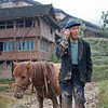 Farmer Ruins My World View<br /> (Longsheng Rice Terraces)<br /> I came across many rural farmers while traveling through the Longsheng (Dazhai ) rice terraces in China who have been working the land and eking out a living like countless generations before them had.  I remember that I had woken up stupid early to squeeze in as much photography time on my last day here.  I woke up and dressed in the dark and stepped out to the cold morning chill only to find my little friend standing outside my hotel, waiting for me to start the day.  This little kid had taken to me and was determined to be my shadow.  We floated in and out of temporary unoccupied houses while the owners were out farming.  About mid-morning, we took a break and sat down to watch the rice farmers do their thing.<br /> <br /> As I watched this old farmer till the land with this trusty horsie I began to wondered what their life would be like if they had access to modern day technology – would their lives be easier?  Perhaps technology would deconstruct their way of life, making it no longer useful or relevant?  I was lost in my own head thinking about the ramifications when all of the sudden the nice farmer stops pushing the horsie, reached in his pocket and pulled out a cell phone.  He proceeded to have a chat with the person on the other end as I stared in complete disbelief.  For all I knew he was talking to his trader to buy stock in Apple before the next iPhone launch.  Even the horse was acting like this is a completely natural.  Sheesh … way to ruin my world view rice farmer.