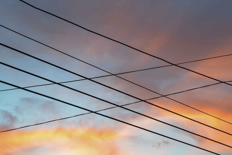 Lines  I recently had to take an emergency trip down to Mexico.  I was really not in the mood to take pictures but it is now second nature to bring my camera everywhere I go, so I had it on me when I was watching the sunset from the rooftop of a house from my youth.  I had quietly sneaked away to be alone for a while and watch the day finally come to a rest.  My vantage point was far from beautiful with the crisscross of power lines dividing the sky into rectangles, almost as if I were watching the sky change color from behind an enclosure, but it felt right and it felt like home.