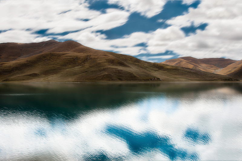 A Place From My Dreams  The Tibetan pleatueau was vast nearly beyond my perception. Instead, I had to experience it in a few different ways:   Time – The more time I spent under its imense sky, the more aware I became of of how insignificant my thoughts were and they slowly silenced.  Distance – I would drive for hours and hours surrounded by raw natural beauty and the more distance I covered, the less I seemed to move through space.  Sight – All my other senses were periferal to sight. I focused all my attention on what I was seeing around me.  It is no wonder, that when I look back on the trip it all seemed like a place from my dreams.