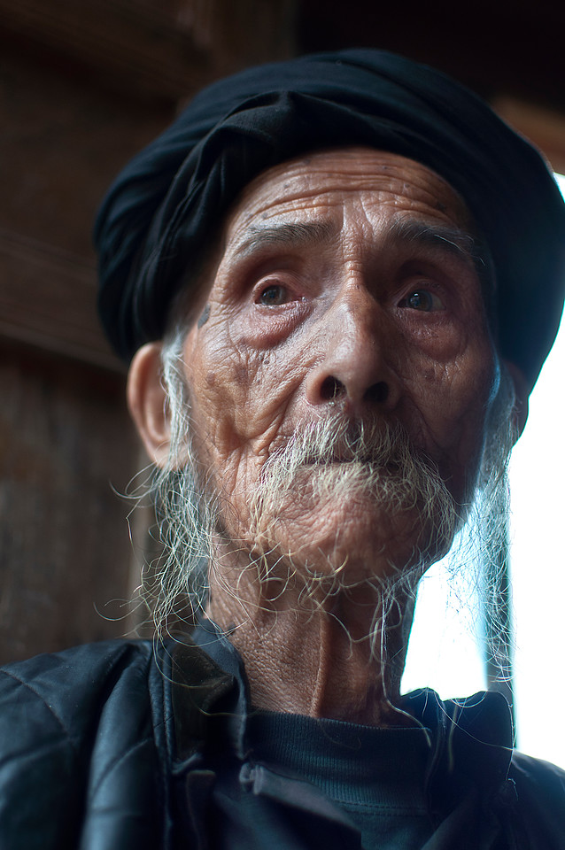 "The Passage of Time<br /> <br /> I met this old man during my trek through the mountain town of Dazhai, China. My guide, Bart, and I were making our way back from the rice terraces when he recognized one of the old wooden houses build on the side of one of the mountains. He asked if I wanted to meet a very old man and I excitedly said yes. We knocked on the old weathered door and someone let us in. After a couple of minutes this old man came out wearing a wide toothless-smile and holding a tobacco pipe which he proceeded to light. He looked so frail but he moved about with a sense of purpose that beguiled his old age. I don't speak Chinese so I did not even bother talking but sometimes you can understand so much by simply observing. I gave him the international sign for ""Can I take your picture?"" and he nodded yes, so I pretended to capture the essence of his life for a few moments.<br /> <br /> Can you imagine what it must be like to live to be ninety years old? To go through a transition of boundless energy and relevance to becoming sedentary and potentially forgotten? You would have lived and loved, served and fought, and made innumerable impressions on other lives. It would afford you with the depth of experience and clarity of vision to look back and divine the things of real worth. From that vantage point you may caution those just starting the journey to be more diligent about their interactions and to take care for the relations they make along the way. I guess we can only hope that the passage of time be kind to us and leave us with the type of memories and experiences that enrich our existence."