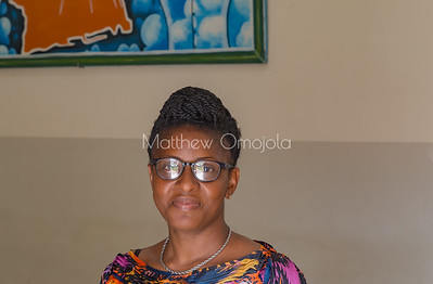 Beautiful smiling Ivorian lady in Yamoussoukro Ivory Coast posed for a picture. Nice African hair style, braiding. She has a pair of glasses on. She is wearing a neck chain. Great complexion,