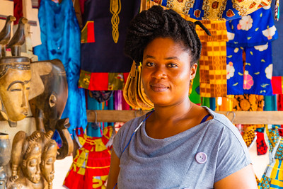 Smiling Ivorian lady vendor in a roadside kiosk selling African Arts, craft, cultural and gift items and materials  in Yamoussoukro Ivory Coast, Cote d'Ivoire. She has a beautiful African hair style, braiding, Nice complexion. Happy