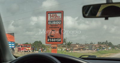 Road sign and roadside activities on the way to Yamoussoukro from Abidjan Ivory Coast Cote d'Ivoire.