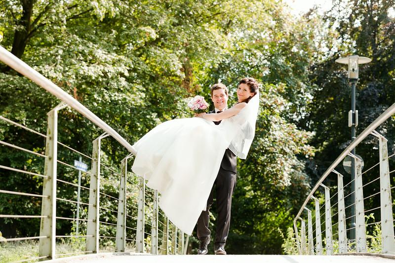 Ein starker Bräutigam trägt die Braut über die Brücke