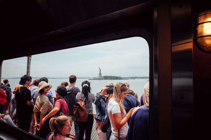 Tourists take in the Statue of Liberty from the deck of the Staten Island ferry, July 2017.