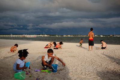 Children play in the sand under stormy skies and rising winds. Gulfport Beach, July 5, 2018.
