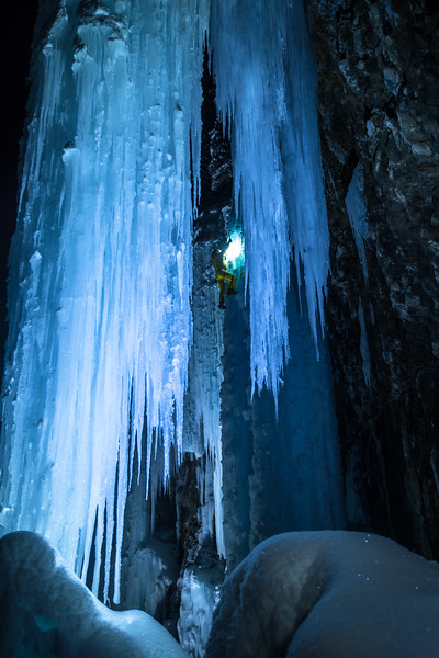 Shot from behind the curtains of ice, Phil climbs the main pillar.