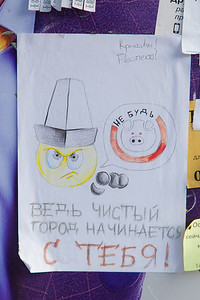 """Hand made sign seen in a bus stop, in Russian language, with a smiley/upset face wearing the traditional Kyrgyz hat: """"Don't be a pig. A clean town starts with you!"""""""