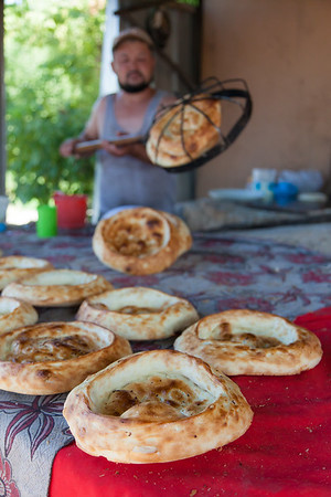 Bread maker on the outskirts of the capital Bishkek. The Kyrgyz people shows hospitality, but on my Western eyes also a bit of naivety/innocence. After taking his pictures, he insisted on giving me the bread for free, and refusing would have been offensive to him. This bread is called Nan or Lepeshka.