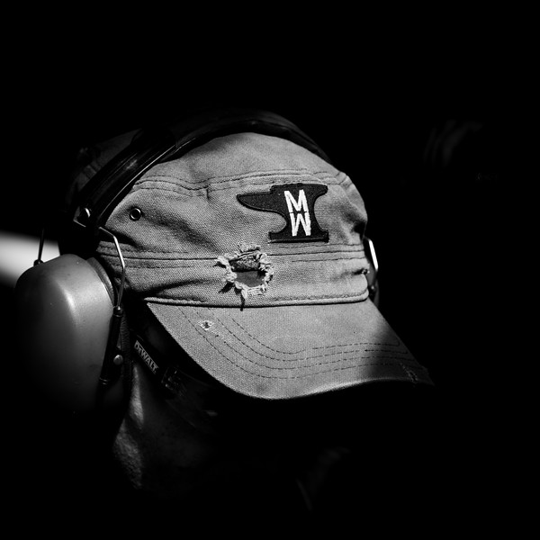 Natural light falls through the window to highlight his branded workwear.