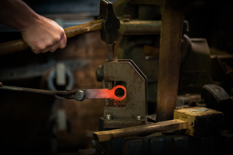 Time to make the neck and handle. Martin smashes the hammer down on the Ozo Tools guillotine tool. Shards of molton metal break away from the force of the blow.