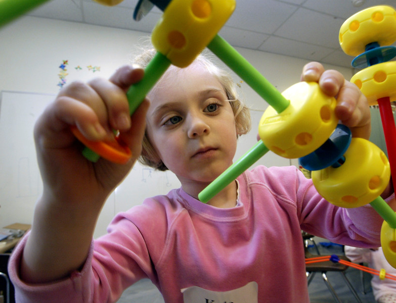 john green/staff 6/23/05 smc times news Kate Flynn,5,builds  a bridge with Tinker Toys, at Camp Galileo in Hillsborough, Thursday morning. The camp includes Science,Art and Outdoor classes.