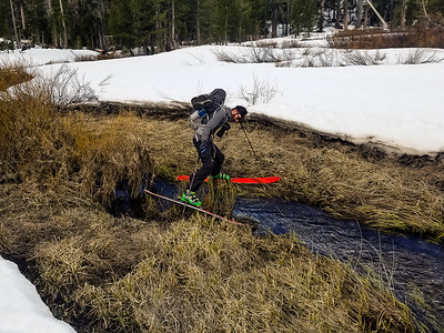Crossing melted out river on skis