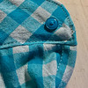 I could have ripped out the whole damn cuff and installed a new one, but I literally don't have time for that shit. (Literal on the time part, not the shit part.) So I ripped out the buttonhole stitching and mended that hole right on up. Didn't even change the thread. I had the turquoise on for sewing on the buttons, and it worked pretty well if you ask me.<br /> <br /> I did have to move the button over a little closer to the edge to get the plaid to line up correctly, so if you look really closely at my wrist, you can see the mending. But who's going to get that close to my hand?