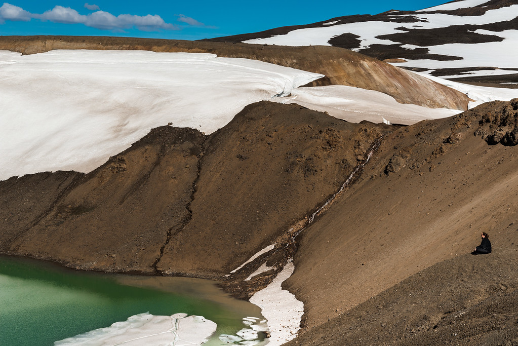 Tourist sitting on the edge of Viti crater Iceland