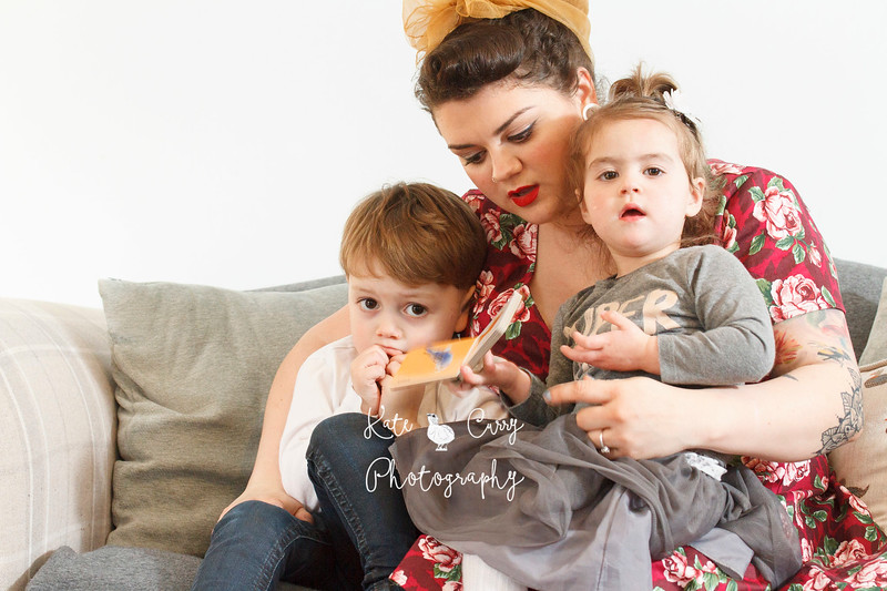 Vintage styled mother sitting on a sofa with her young children